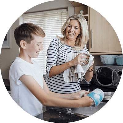 Mother and son wash dishes together using a hand dish soap liquid preserved with Kalaguard SB
